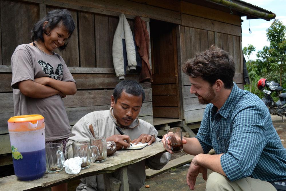 Hier gibt Kaffeebauer Lamhot Andreas seine Kontaktdaten vor seinem Haus, Seine Frau schmunzelt darüber, wie Andreas seinen Namen ausspricht und wie konzentriert ihr Mann schreibt.