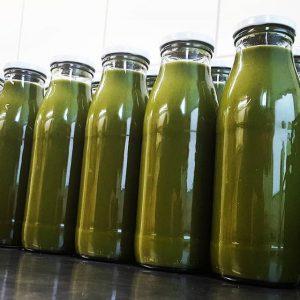 Grüner Saft von Pressgut in Flaschen
