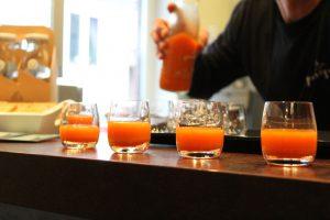 Orangener Saft von Pressgut in Gläsern